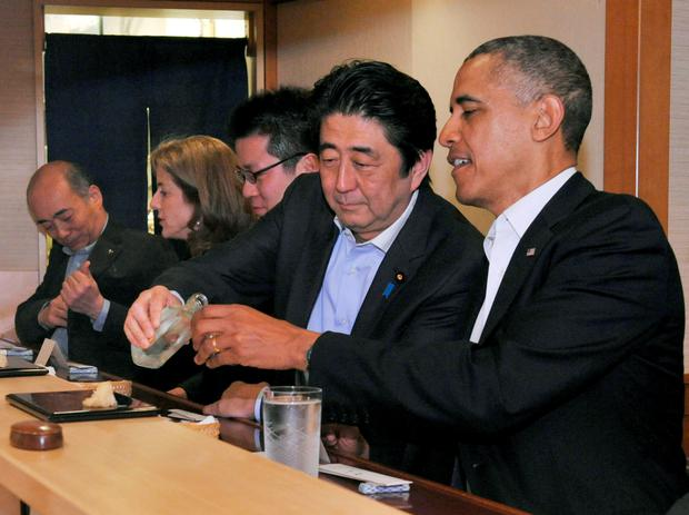 Japanese Prime Minister Shinzo Abe pours sake for then U.S. President Barack Obama as they have dinner at the Sukiyabashi Jiro sushi restaurant in Tokyo, in this file picture taken April 23, 2014. Japanese Cabinet Public Relations Office/Handout via Reuters/File Photo