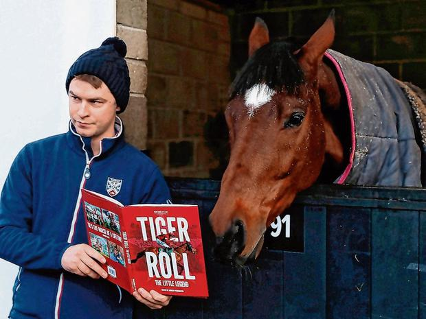 Leon Carroll with two-time Grand National winner Tiger Roll and the new book on the horse during a visit to Gordon Elliott's Cullentra yard. Photo: Brian Lawless/PA Wire