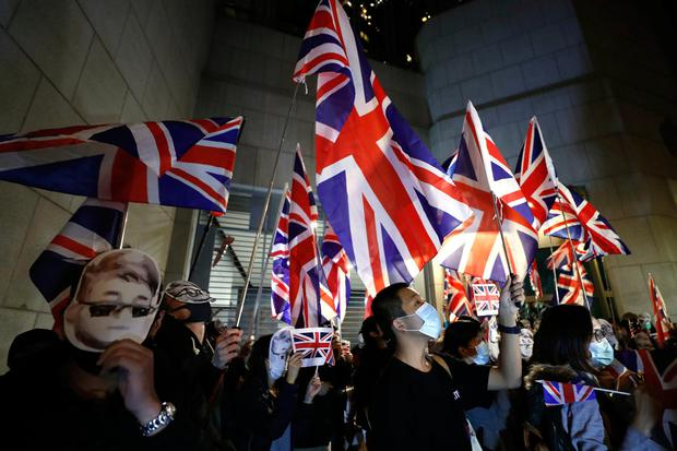 Protesters wave British flags as they gather for a rally outside of the British Consulate in Hong Kong. Image: AP Photo/Vincent Thian