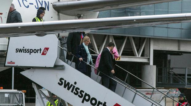 Relieved: Lisa Smith, with a pink blanket over her head, is escorted from the Turkish Airlines aircraft that brought her back. Photo: Mark Condren
