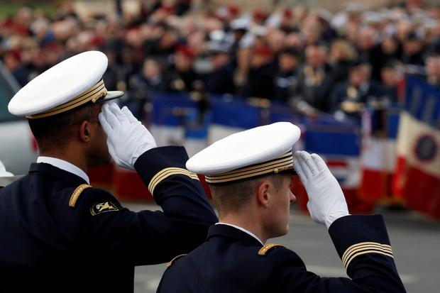 Soldiers and citizens pay tribute as hearses with the coffins of late thirteen French soldiers killed in Mali make their way past the Alexandre III bridge before a ceremony at the Hotel National des Invalides in Paris, France, December 2, 2019. REUTERS/Gonzalo Fuentes