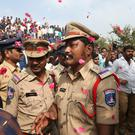 People throw flower petals on the Indian policemen guarding the area where four rape accused were shot, in Shadnagar some 50 kilometers or 31 miles from Hyderabad, India, Friday, Dec. 6, 2019. Picture: AP Photo/Mahesh Kumar A