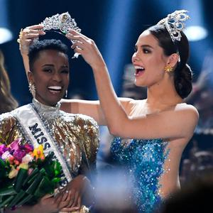 Miss Universe 2018 Philippines' Catriona Gray puts the crowns on the head of the new Miss Universe 2019 South Africa's Zozibini Tunzi on stage during the 2019 Miss Universe pageant at the Tyler Perry Studios in Atlanta, Georgia on December 8, 2019. (Photo by VALERIE MACON / AFP)