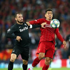 Roberto Firmino of Liverpool battles for the ball with Andreas Ulmer of FC Salzburg at Anfield