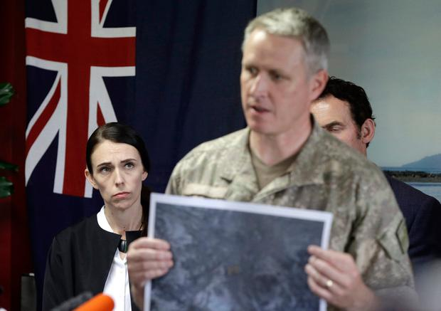 New Zealand Prime Minister Jacinda Ardern, left, watches as Col. Rian McKinstry addresses a press conference following the recovery operation to return the victims of the Dec. 9 volcano eruption off the coast of Whakatane New Zealand, Friday, Dec. 13, 2019. (AP Photo/Mark Baker)