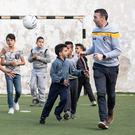 Oisín McConville gives a Gaelic football skills session to young Palestinian refugees in the Aida refugee camp in Bethlehem. He was promoting Trócaire's Christmas appeal to support families in conflict zones. Photo: Garry Walsh/Trócaire.