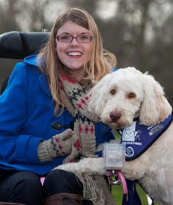 Katy Evans, 24 from Rednal, who was born with cerebral palsy with her assistance dog Crossbreed Folly, during their Crufts 2015 shortlist announcement in Green Park, London for the Eukanaba Friends for Life competition, which celebrates uplifting stories of friendship in adversity. PRESS ASSOCIATION Photo. Picture date: Monday February 23, 2015. See PA story ANIMALS Crufts. Photo credit should read: Hannah McKay/PA Wire