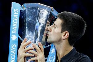 Novak Djokovic holds the men's singles trophy following Roger Federer's withdrawal during the Barclays ATP World Tour Finals at The O2 Arena, London. Photo credit: Jonathan Brady/PA Wire.