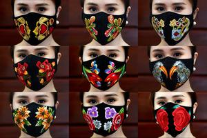 Covered: A model poses in colourful hand-embroidered face masks at her workshop in Hanoi. Photo: Nhac NGUYEN/AFP