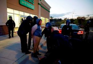 """Baltimore police officers tackle and arrest looters after they emerged from a """"Deals"""" store with merchandise during clashes between rioters and police in Baltimore, Maryland.Photo: Reuters"""