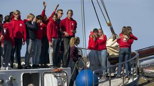 Dutch teenagers on board the schooner they helped sail across the Atlantic arrive at the port of Harlingen (Peter Dejong/AP)