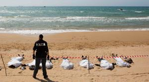 A policeman stands next to the bodies of migrants who drowned on the beach in the Sicilian village of Sampieri September 30, 2013. At least 13 people on a migrant boat arriving in Sicily drowned close to the coast near the eastern city of Ragusa, apparently after trying to disembark from their stranded vessel, Italian authorities said on Monday. Officials said the boat was carrying around 250 people but there was no immediate word on where they came from.  REUTERS/Gianni Mania (ITALY - Tags: DISASTER)