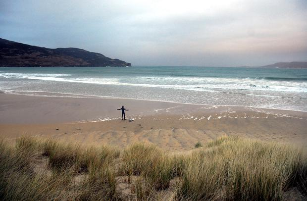 A surfer prepares to take to the waves at Dunfanaghy, Co Donegal. Photo: Pól Ó Conghaile