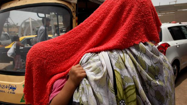 A child grabs her mother's scarf as they are both covered with a water-soaked towel, to beat the heat, in Karachi, Pakistan