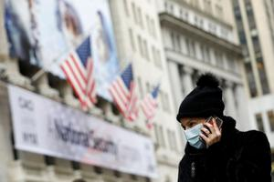A woman in a surgical mask uses her cellphone after more cases of coronavirus were confirmed in Manhattan, New York City. Photo: REUTERS/Andrew Kelly