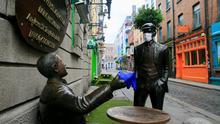 Cover up: Face masks feature on statues beside the Oliver St John Gogarty pub in Temple Bar. Photo: Gareth Chaney, Collins