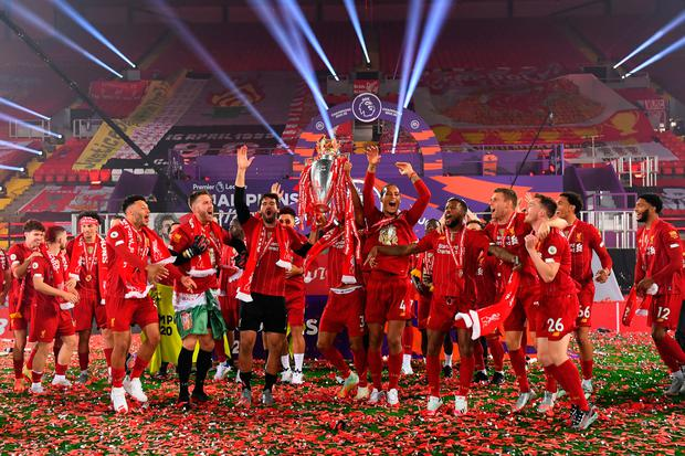 Liverpool players celebrate with the Premier League trophy after the Premier League match at Anfield, Liverpool
