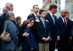 The family of Martin Richard including Bill Richard and other members of the victims families stand during a wreath-laying ceremony commemorating the one-year anniversary of the Boston Marathon bombings on Boylston Street near the finish line