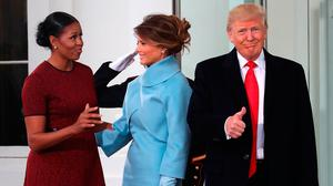 President-elect Donald Trump gives a thumbs up, as his wife Melania Trump (C), first lady Michelle Obama, upon arriving at the White House on January 20, 2017 in Washington, DC. Later in the morning President-elect Trump will be sworn in as the nation's 45th president during an inaugural ceremony at the U.S. Capitol.   (Photo by Mark Wilson/Getty Images)