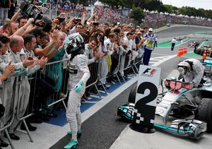 Mercedes Formula One driver Nico Rosberg of Germany celebrates as he steps out of his car after winning the Brazilian Grand Prix in Sao Paulo