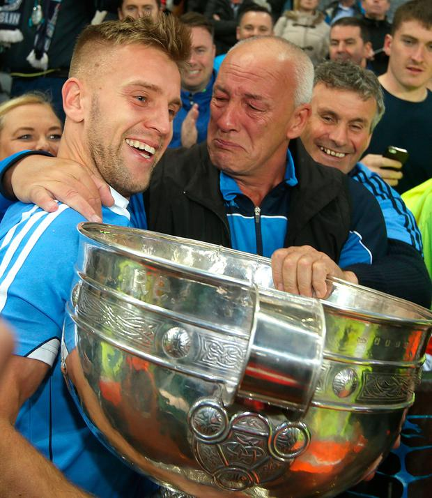 Dublin's Johnny Cooper holds the Sam Maguire cup with his father Brendan Picture: Damien Eagers