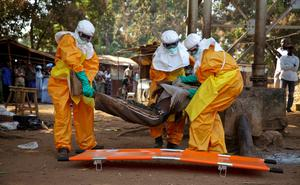 A French Red Cross team picks up a suspected Ebola case from the centre of Forecariah.