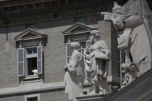 Pope Francis leans out of the window of his private library overlooking St Peter's Square (Alessandra Tarantino/AP)
