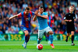 James McArthur of Crystal Palace is challenged by Sergio Aguero