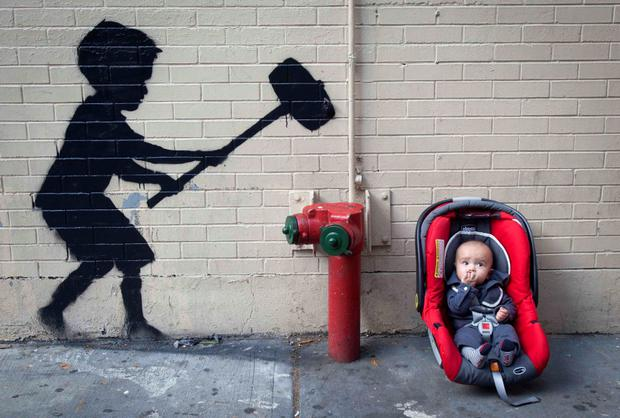 A baby rests next to a new installation of British graffiti artist Banksy's art in New York