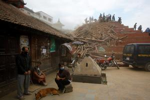 A Nepalese man stands with his dog as rescue workers remove debris at Durbar Square after an earthquake in Kathmandu, Nepal, Saturday, April 25, 2015. A strong magnitude-7.9 earthquake shook Nepal's capital and the densely populated Kathmandu Valley before noon Saturday, causing extensive damage with toppled walls and collapsed buildings, officials said. (AP Photo/ Niranjan Shrestha)