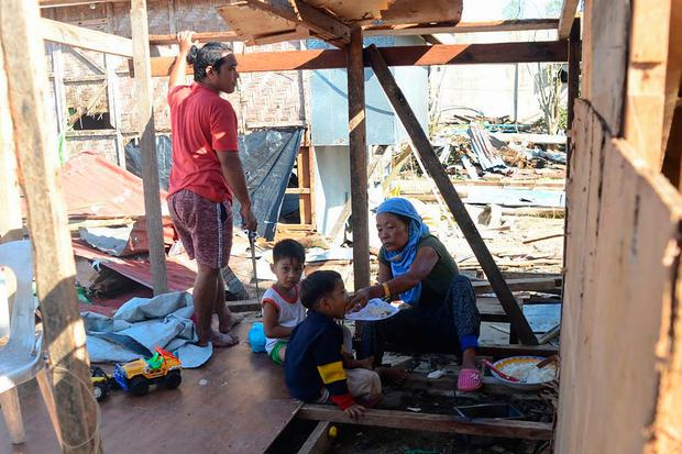 A family eat a meal inside their house damaged at the height of Typhoon Phanfone in Guiuan town in Eastern Samar province on December 26, 2019. (Photo by ALREN BERONIO/AFP via Getty Images)