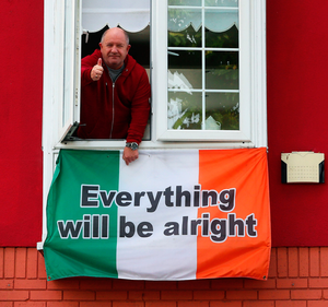 John Maguire gives a thumbs up as he adjusts a flag hanging from the window of his home in Dublin city centre