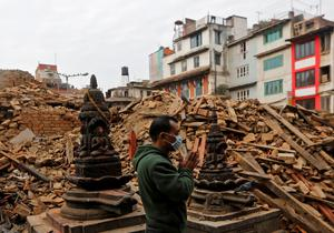 A man prays next to rubble of a temple, destroyed in Saturday's earthquake, in Kathmandu, Nepal April 28, 2015. REUTERS/Adnan Abidi