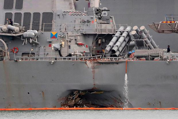 The damaged port aft hull of USS John S. McCain, is seen while docked at Singapore's Changi naval base on Tuesday, Aug. 22, 2017 in Singapore. (AP Photo/Wong Maye-E)