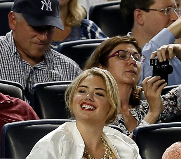 Supermodel Kate Upton smiles as she sits in the seats above the Detroit Tigers dugout in a baseball game between the Tigers and the New York Yankees at Yankee Stadium in New York, Monday, Aug. 4, 2014. (AP Photo/Kathy Willens)