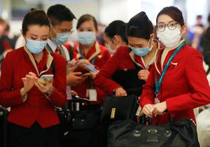 Alert: A flight crew from Cathay Pacific Airways, wearing protective masks, pass through the international terminal at Los Angeles International Airport, California. Photo: Mario Tama/Getty Images