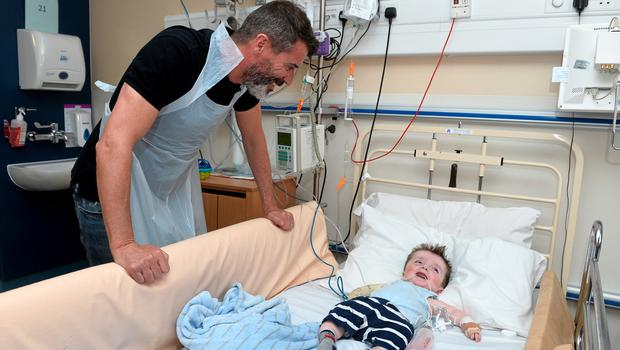 11 June 2015; Republic of Ireland manager Martin ONeill and assistant manager Roy Keane took time out of their busy preparation for Saturdays must win qualifier against Scotland to make a very special visit to Temple Street Childrens University Hospital today, where they met brave little patients, along with their parents and staff. The Irish legends made the visit in conjunction with the SportsWorld FAI Summer Soccer Schools, who earlier this year announced Temple Street as their charity of the year. SportsWorld, part of the Heatons department store group, are delighted to be title sponsor of the FAI Summer Soccer Schools. You too can support Temple Street Childrens Hospital by donating 1 when you book your camp online at www.summersoccerschools.ie. Pictured are Republic of Ireland assistant manager Roy Keane with John Mahon, age 18 months, from Blanchardstown, Co. Dublin. Temple Street Hospital, Dublin. Picture credit: David Maher / SPORTSFILE