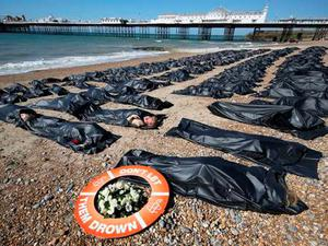 Amnesty International volunteers lie in 200 body bags on Brighton beach to highlight the migrant crisis in the Mediterranean (Getty)