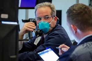 A trader wears a face mask on the floor of the New York Stock Exchange (NYSE) following traders testing positive for Coronavirus disease (COVID-19), in New York