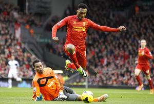 Liverpool's Daniel Sturridge leaps over Swansea goalkeeper Michel Vorm and scores his teams opening goal