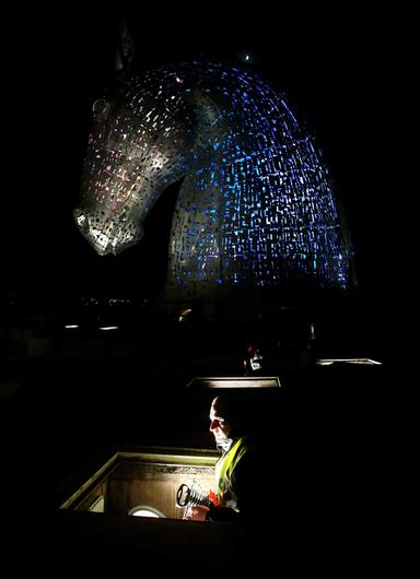 Electrical Engineer Stewart Donaghy beside one of the Kelpies as a lighting test is carried out on the Kelpies in Falkirk ahead of their  official opening to the public later this month. PRESS ASSOCIATION Photo. Picture date: Monday April 7, 2014. Designed by sculptor Andy Scott each of The Kelpies stands up to 30 metres tall and each one weighs over 300 tonnes. They are constructed of structural steel with a stainless steel outer skin, they pay homage to the tradition of working horses of Scotland which used to pull barges along Scotland's canals.  They stand at the entrance to the North Sea at the Forth and Clyde canal. Photo credit should read: Andrew Milligan/PA Wire
