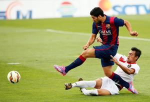 Barcelona's Luis Suarez shoots and scores a goal against Indonesia U19 player Hansamu Yama during today's friendly