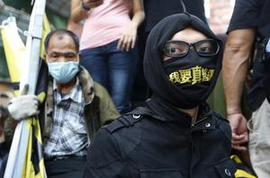 A pro-democracy protester with a mask takes part in a rally at an occupied area in Mong Kok district of Hong Kong Tuesday, Nov. 25, 2014.  (AP Photo/Kin Cheung)