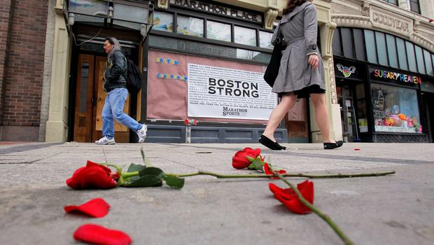 Flowers lie on the sidewalk at the site of the first explosion as people walk along Boylston Street after the street reopened to the public for the first time since the Boston Marathon bombings in Boston, Massachusetts in this April 24, 2013 file photo. Tuesday marks the one-year anniversary of theBostonMarathonbombing on April 15, 2013, when two Chechen brothers allegedly planted pressure-cooker bombs near the race's finish line, killing three people and wounded more than 260.  REUTERS/Jessica Rinaldi