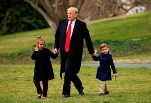 Restrained: People need to remember that US President Donald Trump, pictured here holding hands with his grandchildren Arabella and Joseph outside the White House, has to act within the boundaries of the American constitution. Photo: Reuters/Kevin Lamarque