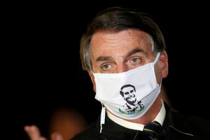 Leader: Jair Bolsonaro wears a mask bearing an image of himself as he speaks to reporters in Brasilia at the weekend. Photo: Reuters/Adriano Machado