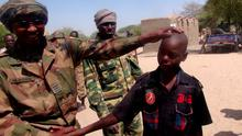 A Chadian soldier embraces a former child soldier of insurgent group Boko Haram in Ngouboua, Chad, April 22, 2015. The young men said they were Chadian nationals forced to join Boko Haram while studying the Quran in Nigeria, and that they escaped and turned themselves in to Chadian authorities. Picture taken April 22, 2015. REUTERS/Moumine Ngarmbassa