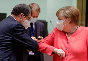 Cypriot President Nicos Anastasiades and Germany's Chancellor Angela Merkel bump elbows at the start of the first face-to-face EU summit since the coronavirus disease outbreak, in Brussels, Belgium July 17, 2020. Stephanie Lecocq/Pool via REUTERS