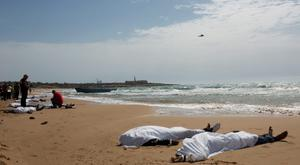 Bodies of migrants who drowned lie on the beach in the Sicilian village of Sampieri September 30, 2013. At least 13 people on a migrant boat arriving in Sicily drowned close to the coast near the eastern city of Ragusa, apparently after trying to disembark from their stranded vessel, Italian authorities said on Monday. Officials said the boat was carrying around 250 people but there was no immediate word on where they came from. REUTERS/Gianni Mania (ITALY - Tags: DISASTER)