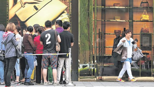 Customers wait outside a Gucci Store offering a 50pc discount in the Golden Eagle Shopping Centre in Shanghai, China. Photo: Getty Images
